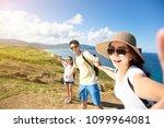 happy family taking selfie on... | Shutterstock . vector #1099964081