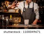 bartender adding an alcoholic... | Shutterstock . vector #1100049671