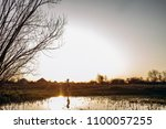 the small girl stands near lake | Shutterstock . vector #1100057255