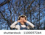 the small girl stands near trees   Shutterstock . vector #1100057264
