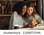 two women sitting in a... | Shutterstock . vector #1100071544