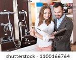young couple choosing new... | Shutterstock . vector #1100166764