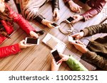 many hands using smartphones in ... | Shutterstock . vector #1100253251