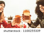 Small photo of girls drinking beer and toasting with pint glasses. happy cheerful multi ethnic girlfriends smiling and saying cheers. concept of diversity, drinking, fun and toothy smiles