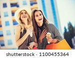 happy young women with shopping ... | Shutterstock . vector #1100455364