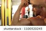fit male admiring his developed ... | Shutterstock . vector #1100520245