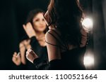 Stock photo beautiful elegant brunette in a black silk dressing gown is standing in front of a tall make up 1100521664