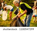 volunteers picking trash at a... | Shutterstock . vector #1100547299