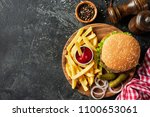 burger and fries on wooden... | Shutterstock . vector #1100653061