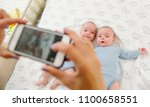 mother takes a photo of her... | Shutterstock . vector #1100658551