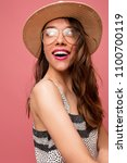 Small photo of Inspired european female model looking aside with happy smile and true emotions in studio and laughing. Winsome brunette girl in cute dress posing on pink background.