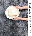 woman hands holding bread in... | Shutterstock . vector #1100705021