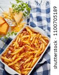 Small photo of aussie fries smothered in melted cheese and bacon in a baking dish on a white wooden table with ingredients at the background, vertical view from above, flat lay