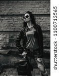Small photo of City girl. Beautiful young woman in black leather jacket and sunglasses posing over brick wall. Black and white