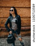 Small photo of City girl. Beautiful young woman in black leather jacket and sunglasses posing over brick wall.