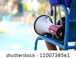 lifeguard sitting on chair with ... | Shutterstock . vector #1100738561