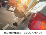 filling gasoline into a car. | Shutterstock . vector #1100775404