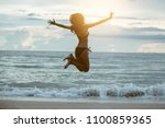 happy asian woman jumping on... | Shutterstock . vector #1100859365