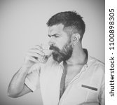 Small photo of Male Face. Issues affecting boy. Hipster drink clean healthy water, refreshing. Health and dieting. Life source and healthcare. Hangover and thirst. Man with long beard hold water glass on grey