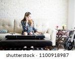 young woman sitting on sofa and ... | Shutterstock . vector #1100918987