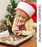 Little girl decorating the christmas cookies - stock photo