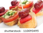 closeup of a plate with different spanish pinchos, like those made with chorizos an red pepper, or tomato and cheese - stock photo
