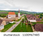 Small photo of Bike route in Cloasterf Saxon Village and Fortified Church in Transylvania, Romania. Cyclist on the road. Bike ride recreation in Romania Bicycle tourists in old village. Group of friends riding bikes