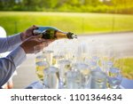 Small photo of Waiter pouring champagne or sparkling wine to glasses at an outdoor VIP event