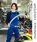 Small photo of happy repairwoman standing near cycle in bicycle store