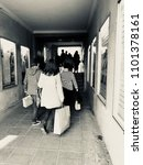Small photo of Back view of people walking with shopping bags in a passage, wearing coat, jacket and striped pullover and long trousers. Both sides of the gangway with illuminated advertising windows. Black'n white.