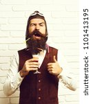 Small photo of handsome bearded aviator man with long beard and mustache on funny face holding glass of alcoholic shot in vintage suede leather waistcoat with hat and glasses on white brick wall backgroun.