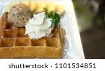 Small photo of Ice cream waffle and banana with honey syrup on white plate on t