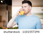 handsome young man drinking... | Shutterstock . vector #1101557294
