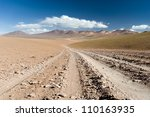 THis image shows a road leading into the colourful high Andean landscape. - stock photo