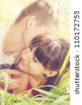 Young couple lying on the grass whispers,tinted - stock photo