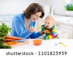 Small photo of Mother feeding child. First solid food for young kid. Fresh organic carrot for vegetable lunch. Baby weaning. Mom and little boy eat vegetables. Healthy nutrition for children. Parents feed kids.