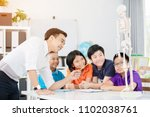 Small photo of Asian teacher explains a human body structure to little pupil.
