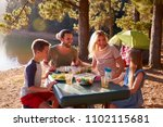family camping by lake on... | Shutterstock . vector #1102115681
