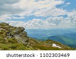 Small photo of A big stone scaur and green hills in Carpathian mountains in the summer. Mountains landscape background.