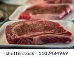 raw seasoned steak on styrofoam ... | Shutterstock . vector #1102484969