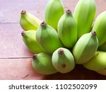Small photo of Cultivated banana yellowish green on a wooden table.Beta carotene Niacin and dietary fiber.Eat banana It helps drain the stomach and can treat scurvy in young children.