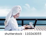 Asian woman in bathrobe with mug of coffee and typing on laptop computer. shot on  ocean view - stock photo