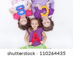 Girls holding A B C letters - laying on the floor - stock photo