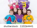 Group of kids holding alphabetical letters - back to school together - stock photo
