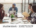Small photo of Happy young man communicating with glad colleagues while sitting at table in modern office. They using laptops at job. Business communication concept