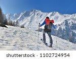 man climbing snowy mountain in... | Shutterstock . vector #1102724954