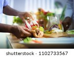 hand of chef holding french... | Shutterstock . vector #1102733567