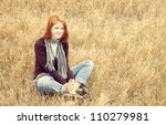 Beautiful red-haired girl sitting at yellow autumn grass. - stock photo