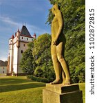Small photo of HRADEC NAD MORAVICI, CZECH REPUBLIC - JUNE 2018: Stone statue of girl looking at the White Tower at Hradec nad Moravici Chateau Complex near Opava, Czech Republic