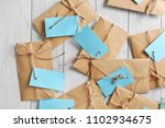 Small photo of Brown envelopes with tags on wooden background, top view. Mail service